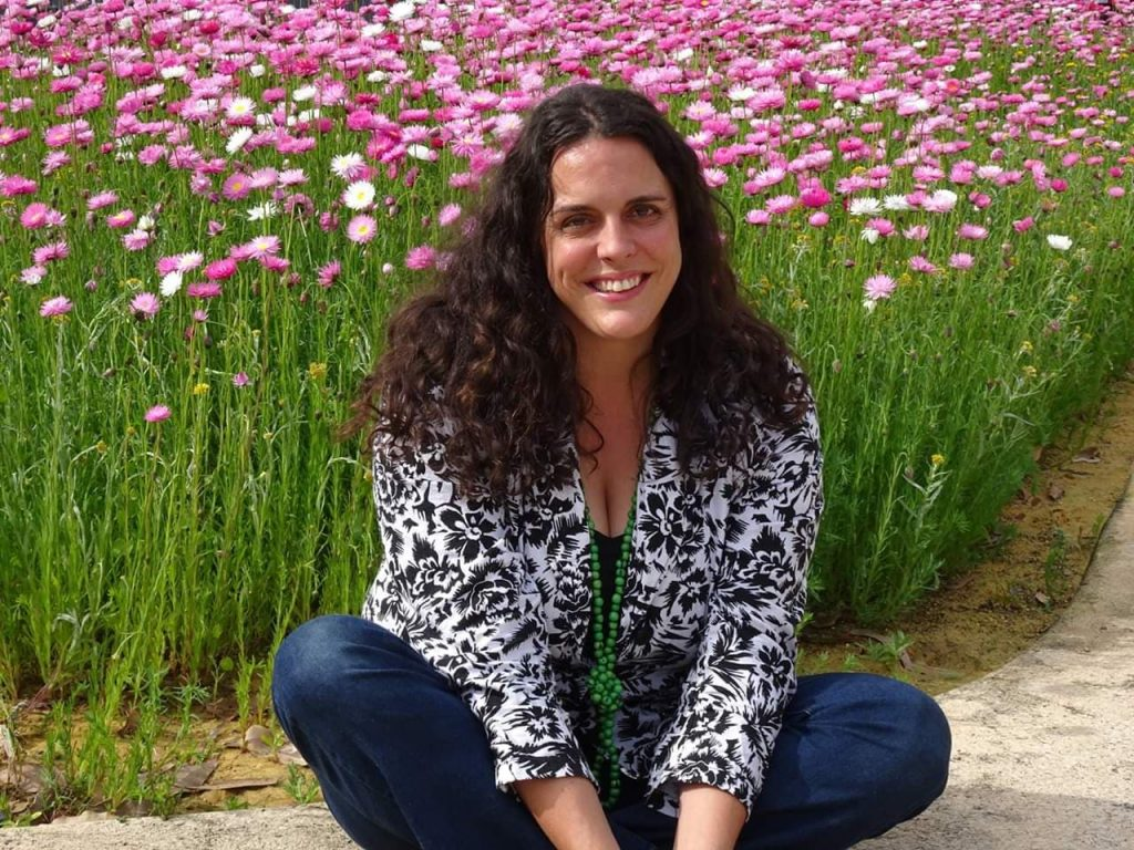 Helen Ansell seated at field of paper daisies